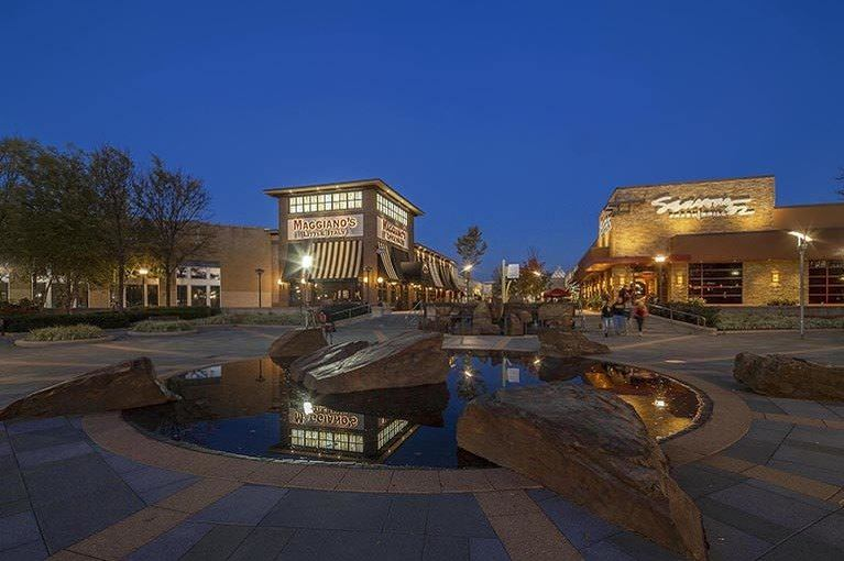 Behind a decorative fountain, restaurants at The Mall in Columbia are illuminated against the night sky.